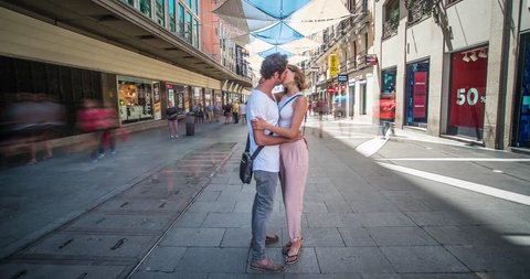 Time lapse of couple of lovers kissing while the people move speedly