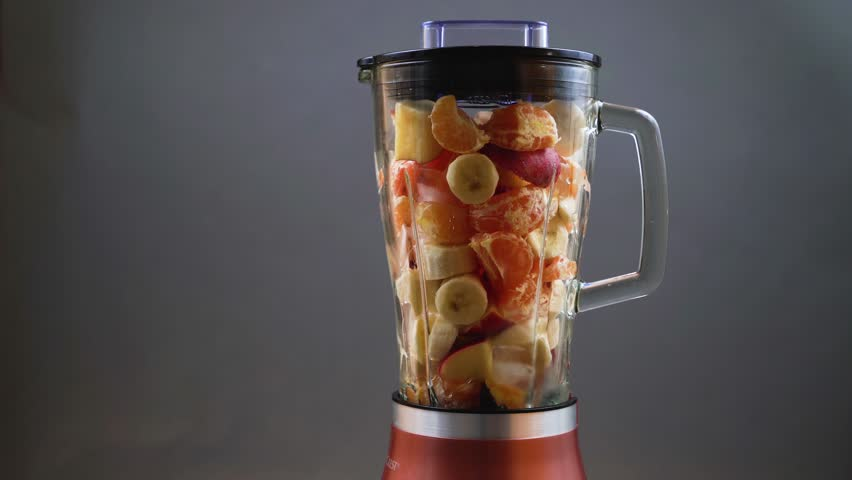 A fresh cocktail of bananas, tangerines, apples and ice is mixed in a blender close-up on a gray background. | Shutterstock HD Video #32161915