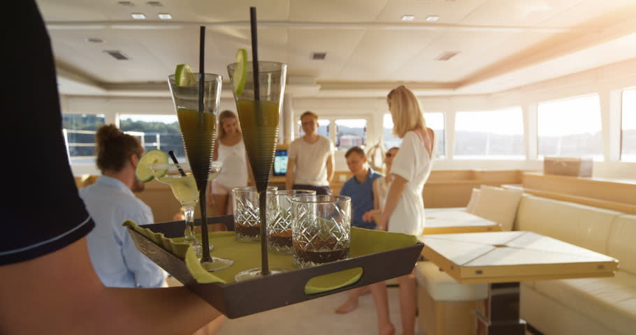 Following Shot of the Waiter Walking with a Tray Full of Exotic Cocktails, Serving them to a Company of Young People on a Yacht. Shot on RED Epic 4K UHD Camera.