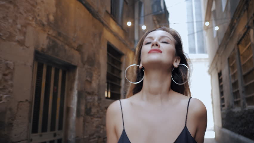 Gorgeous blonde alluring woman in sexy black dress and red lips walking in gothic quarter of Barcelona. Natural beauty, female portrait, seductive look. Being self-confident. 4k