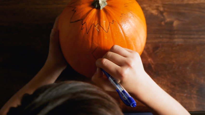 Young boy carving a pumpkin for Halloween on a table