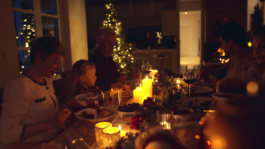 Christmas eve dinner, family sitting at dining table enjoying dinner together. Family celebrating christmas together at home.   Shutterstock HD Video #32229808