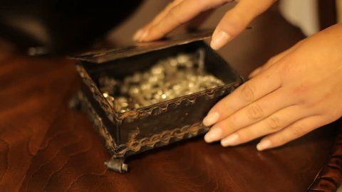 beautiful woman opens the box. well-groomed woman's hand opens a box with jewelery. part of the body. close-up