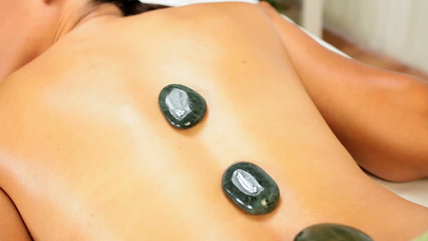 Beautiful ethnic client being treated with hot stone therapy at a luxury health spa