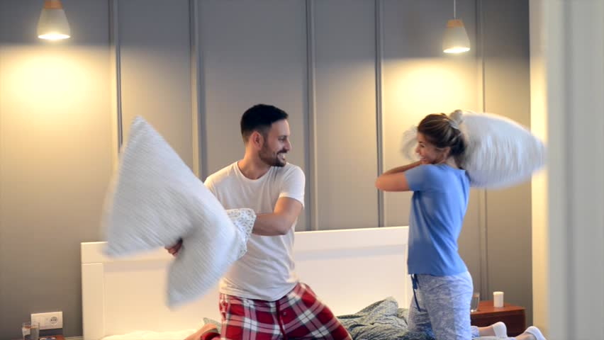 Young pretty lovely couple fighting with pillows on the bed and enjoying time spent together. #32249455
