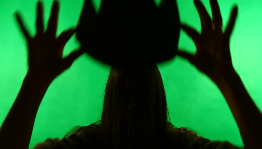 Young adult woman queens or crowns herself against green screen chroma background. Back-lit silhouette.  | Shutterstock HD Video #3225565