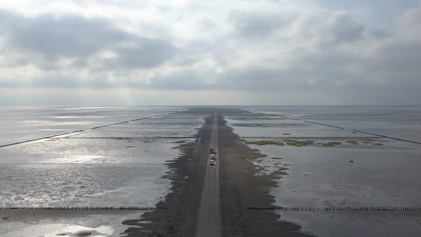 Aerial of Low tide path to the island Mandø in Denmark, only access by car – 4K | Shutterstock HD Video #32264215