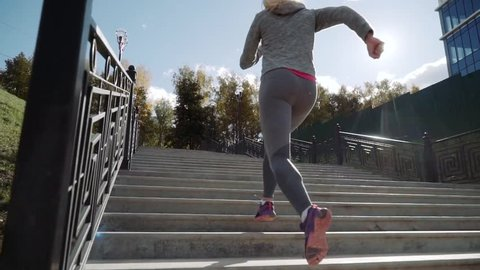 the girl runs up the stairs. The runner runs up the stairs. Slow motion. The camera rises.