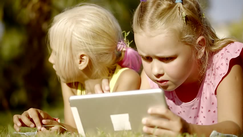 Lovely sisters with a serious face watching cartoons on the tablet, one of the girls touches the leaves that plucked from the ground | Shutterstock HD Video #32288515