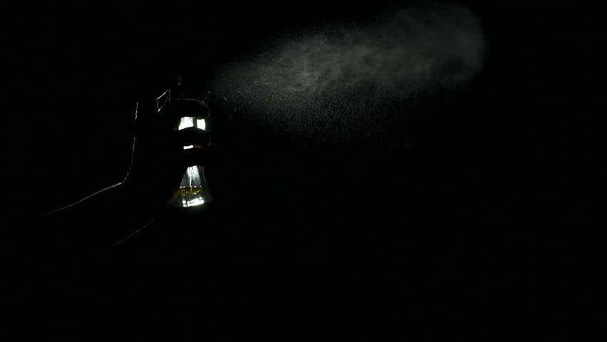 Close-up silhouette of a girl spraying perfume in the dark, slow motion.