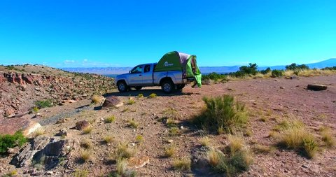 Truck Tent Camper On Ridge Overlooking Rocky Desert Valley In Colorado - Aerial Fly Over Of Campsite