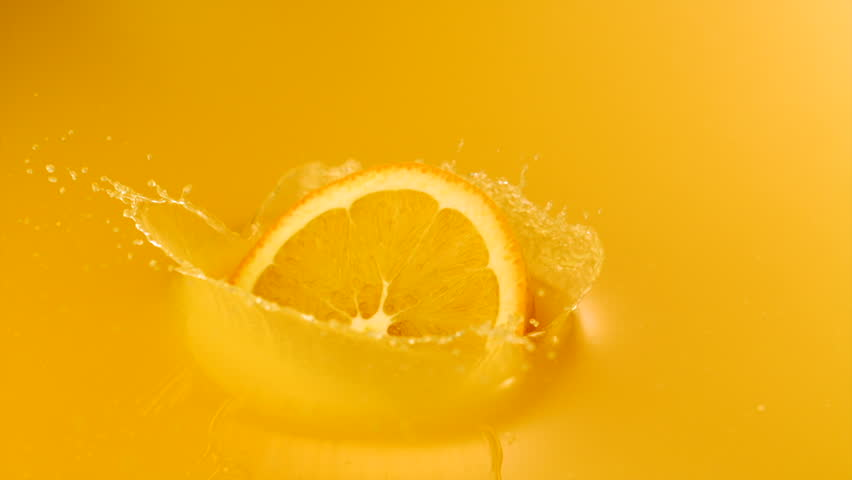 Sliced orange falling into orange juice shooting with high speed camera, phantom flex.