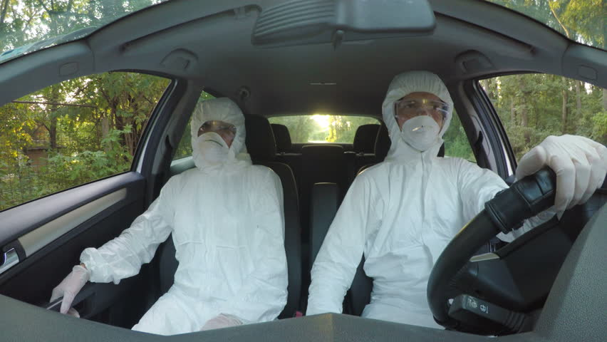 Funny concept of two young hazmat scientists workers in car dancing and driving to contaminated location