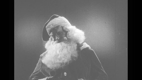 1940s: Santa Claus places finger on nose, gestures with hand and speaks. Santa holds hands over young girl sleeping in bed. Face of sleeping girl. Girl wakes up, sits up in bed, looks surprised.