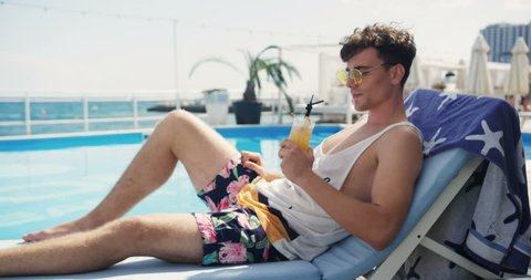 Handsome man in sunglasses look camera smile lays sunbed pool drinks a cocktail male resort sitting luxury resting swimming happiness, summer sunbathing travel vacations hotel looking relaxation sea
