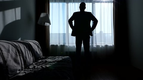 Man in casual suit stay arms akimbo against bright window in living room, black silhouette. Guy with slick hair standing still and contemplate outdoors, light white transparent curtain lit by sunlight