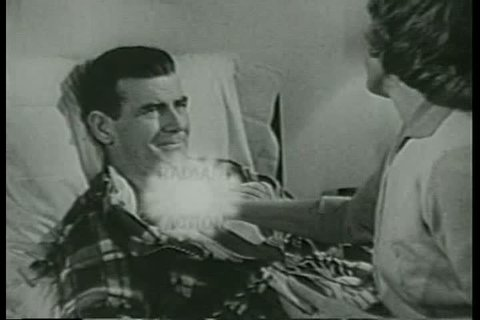 CIRCA 1950s - A wife rubs Ben-Gay ointment on her husbands chest, in a television commercial, in the 1950s.