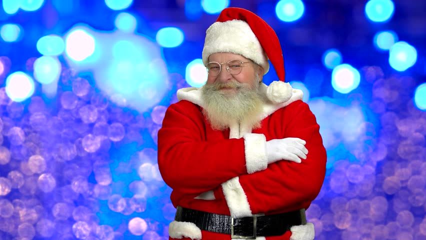 Santa Claus, blurred lights background. Happy Santa, folded arms. New Year resolutions.