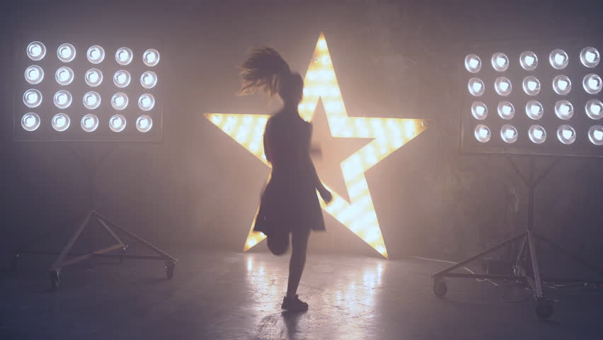 A young professional dancer performs a fast number on stage in the light of the spotlights. a woman in a short skirt and a tall top. A girl is dancing on stage using a smoke machine. Spotlights in the