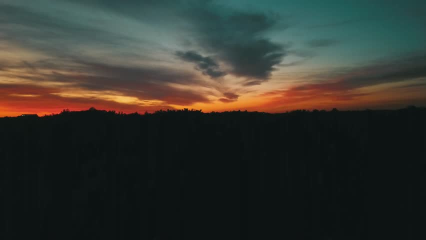 Aerial drone footage of a silhouetted skyline with brilliant sunset colors.