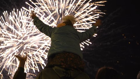 Little girl sitting on your dad's shoulders and watching fireworks. Concept of family relationships and Father's day. Viewers take pictures on smartphone. Firework - concept of finale of any holiday