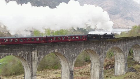 GLEN FINNAN, SCOTLAND - AUGUST 2017: Stunning aerial shot of the Jacobite steam train going over the Glenfinnan viaduct with white steam