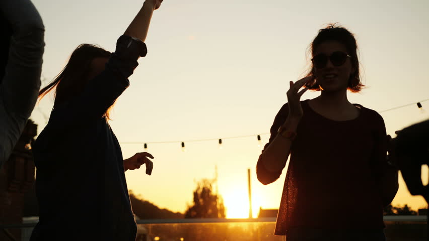 Silhouettes of young people dancing at the rooftop party in urban space. The sunset background. Outside. Multiethnic