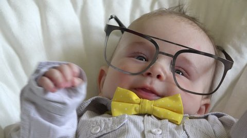 Funny little baby with big eyeglasses and bow tie, boss portrait
