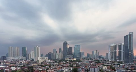 Sunset time lapse, as a day to night video with a zoom out effect, over Jakarta skyline business district in Indonesia capital city. Jakarta is Indonesia capital city and the largest in Southeast Asia