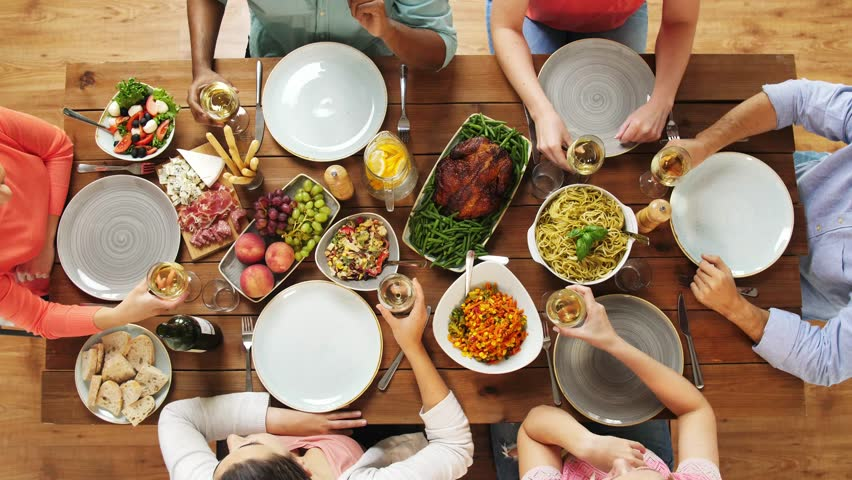 Eating and holidays concept - group of people at table with food clinking wine glasses | Shutterstock HD Video #32420275