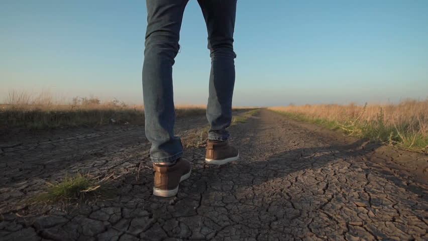 Back view of unknown lone man walking away down a rural road in a low angle view in a conceptual motion clip