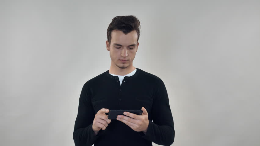 Trendy millennial man using smartphone scrolling touch screen mobile. Young guy looking photo in social media or working with documents. Portrait men using cellular | Shutterstock HD Video #32425825