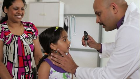 An Indian pediatrician or family doctor listens to the heart of a little girl who is being accompanied by her mother.