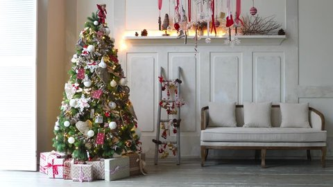 White room with Christmas and New Year interior decoration. Green tree decorated with toys and flashing garland