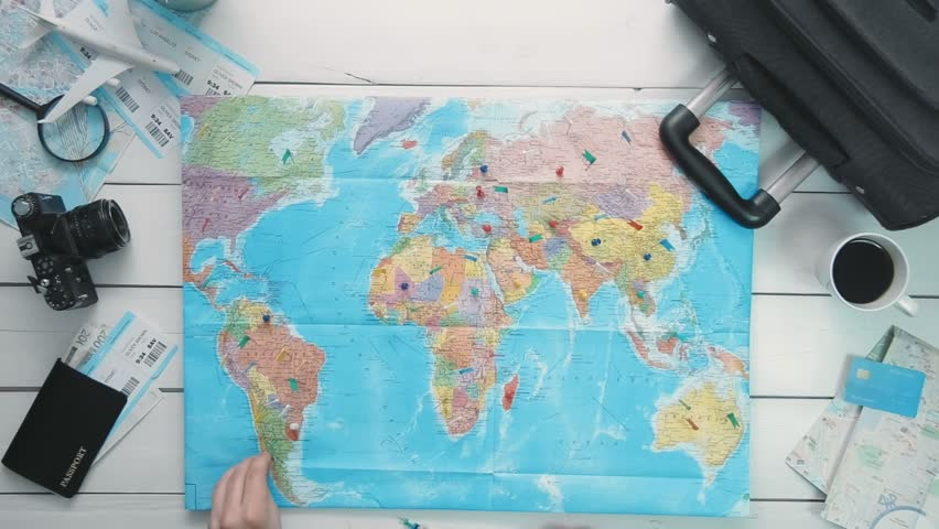 Top view travelers hands looking at world map using magnifying top view time lapse travelers hands putting pins in the map showng countries he has visited gumiabroncs Choice Image