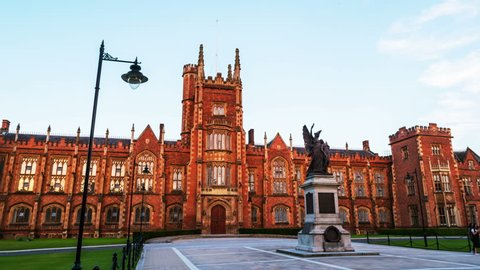 Belfast, UK. The Lanyon Building, Queen's University Belfast, Northern Ireland, UK. Time-lapse in the evening with cloudless blue sky. Moving hyperlapse