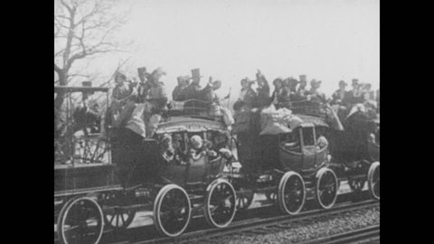 1930s: Early steam train rides on tracks, people ride in carriages, wave. Large steam engine steams down tracks.