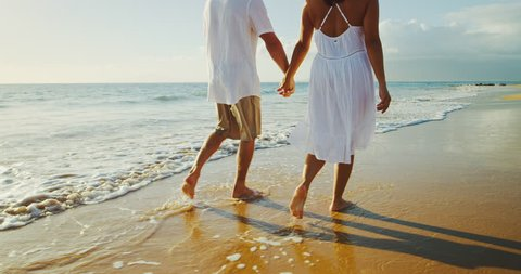 Happy romantic couple walking down the beach at sunset