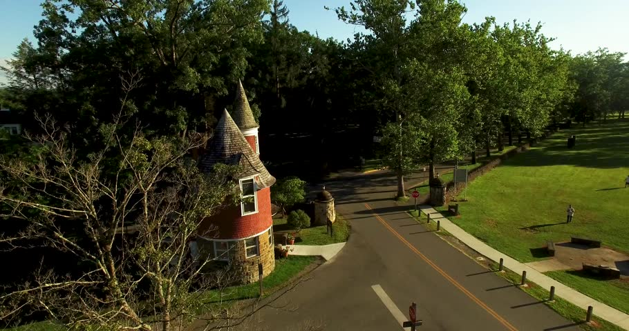Aerial view of Davis & Elkins College Gate House with camera orbiting and then pulling away just before sunset.