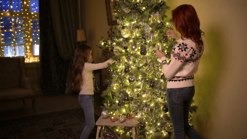 A young attractive woman with her little cute daughter decorating a Christmas tree, smiling and laughing | Shutterstock HD Video #32526475
