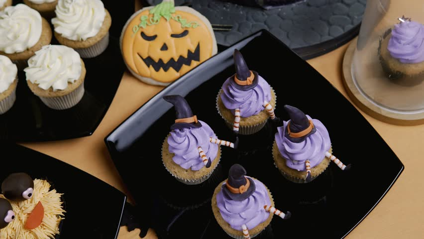 Cupcakes with icing hat and legs. Delicious Muffin like witch. Halloween concept in 4k, UHD