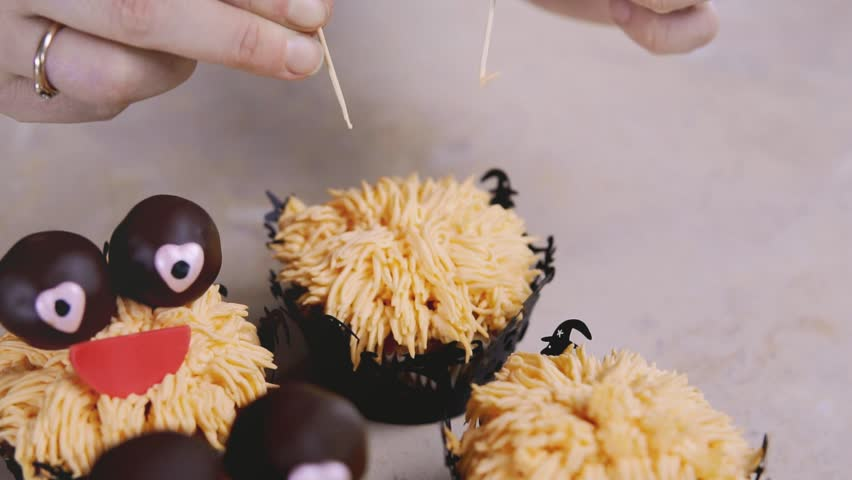 Decorating funny cup-cake with chocolate eyes and red smile. Muffin with Halloween concept. Sweet monster.