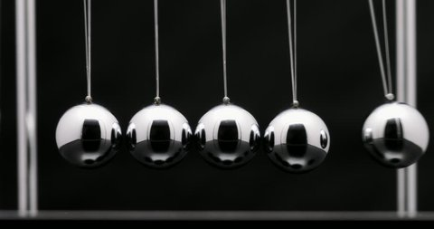 Newton's cradle office toy. Studio shot of swinging metal balls in slow motion on black background