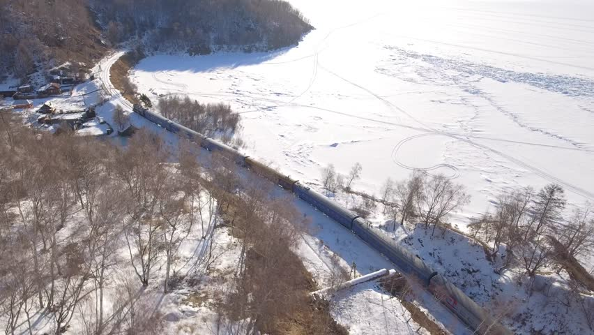 From above top passengers train Trans Siberian railway old village. Frozen lake Baikal coast. Winter beautiful Holiday  Russia. Sunny day snow field high rocks. Fast speed aerial drone 4k footage.