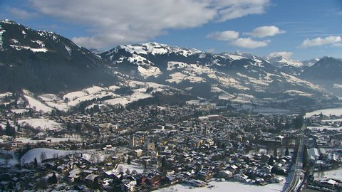 WS AERIAL Snow-covered town in mountain valley / Kitzbuehel, Tyrol, Austria
