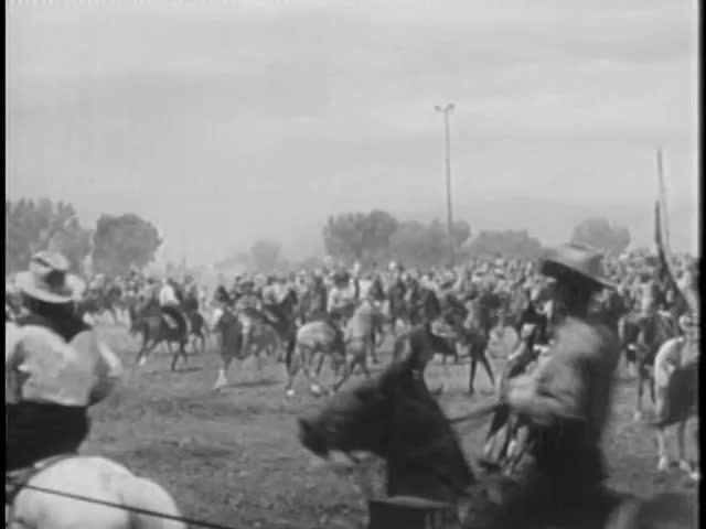 Cowboys on horseback prancing around before rodeo