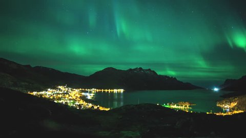 Time lapse of a northern light in northern Norway. Calm fjord and a seashore village