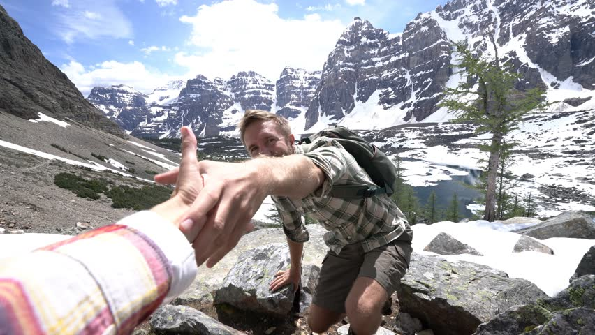 Young man hiking in the Canadian rockies, hand reach out to help. Helping hand, couple hiking, reach mountain top hand reaches out for assistance