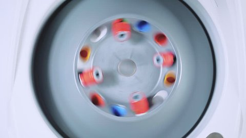 A centrifuge spins vials of liquid in a laboratory test.