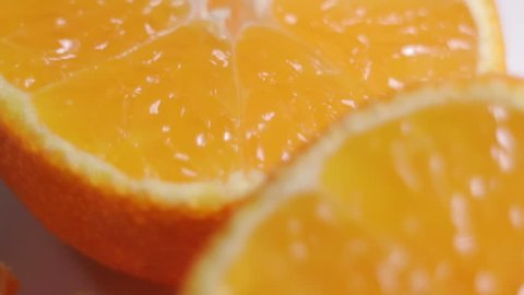 Texture of a cut mandarin orange close-up. Packing grid in the frame. Smooth motion. The focal length changes.